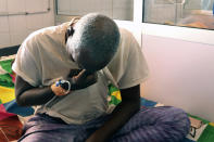 Ousseni Yanogo, 63, sits on his bed at Ouagadougou's Bogodogo Medical Teaching Hospital Thursday Feb. 4, 2021. Yanogo contracted COVID-19 at his 6-year-old grand-daughter's birthday. Since November, the conflict-riddled West African nation of Burkina Faso faces a much deadlier second coronavirus wave than the first and health officials worry a lack of knowledge and adherence to coronavirus measures is making it hard to rein in. (AP Photo/Sam Mednick)