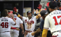 Atlanta Braves outfielder Ronald Acuna gets high fives in the dugout after hitting a solo home run against the Toronto Blue Jays during the third inning of a baseball game on Tuesday, May 11, 2021, in Atlanta. (Curtis Compton/Atlanta Journal-Constitution via AP)