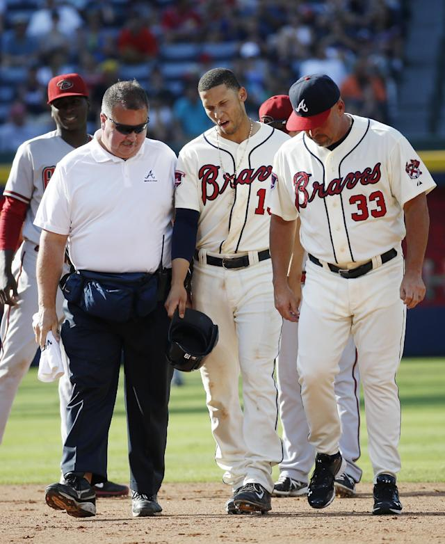Atlanta Braves shortstop Andrelton Simmons, center, walks off the field with assistant athletic trainer Jim Lovell and manager Fredi Gonzalez (33) after being injured in the sixth inning of a baseball game against the Arizona Diamondbacks in Atlanta, Saturday, July 5, 2014. (AP Photo/John Bazemore)