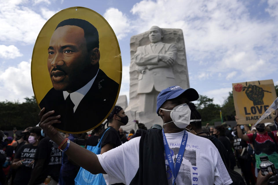 FILE - In this Aug. 28, 2020, file photo, a man holds a photo of Martin Luther King, Jr., at the Martin Luther King Jr. Memorial during the March on Washington in Washington. In the nation's capital on Saturday, Aug. 28, 2021, multiracial coalitions of civil, human and labor rights leaders are convening rallies and marches to urge passage of federal voter protections that have been eroded since the Voting Rights Act of 1965. (AP Photo/Carolyn Kaster, File)