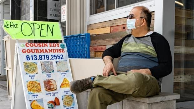 A man sits outside a ByWard Market food vendor on May 10, 2021, during the COVID-19 pandemic's third wave. On Saturday, Ottawa health officials reported 95 new cases and one new death. (Brian Morris/CBC - image credit)