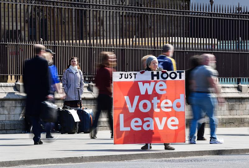 A supporter of Brexit holds a sign saying 'Just hoot, we voted leave' while others continue with their daily activities outside the Houses of Parliament, Westminster, London, ahead of the latest round of debates in the House of Commons concerning Brexit issues.