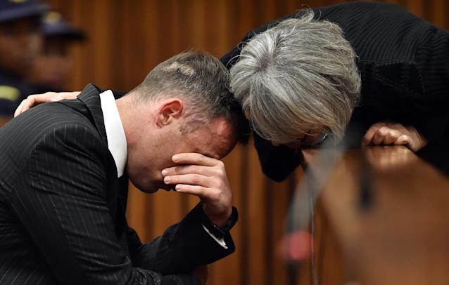 Former Paralympian Oscar Pistorius is comforted by an unidentified woman before his sentencing for the murder of Reeva Steenkamp at the Pretoria High Court, South Africa June 13, 2016. REUTERS/Phill Magakoe/Pool