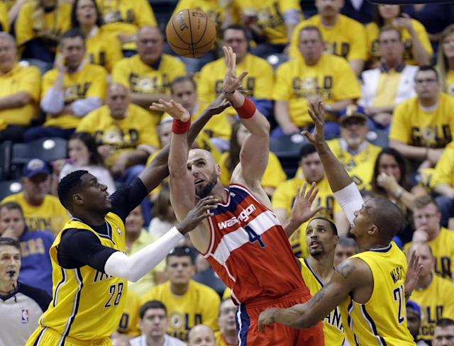Washington Wizards center Marcin Gortat, center, makes a pass over Indiana Pacers center Ian Mahinmi, left, and Indiana Pacers forward David West, right, during the second half of game 1 of the Eastern Conference semifinal NBA basketball playoff series in Indianapolis, Monday, May 5, 2014. The Wizards defeated the Pacers 102-96. (AP Photo/Michael Conroy)