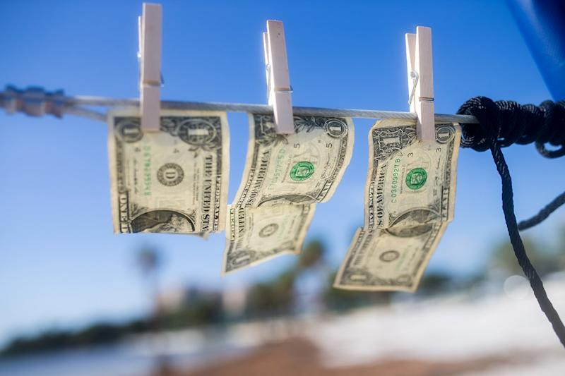 Dollar bills hanging on a clothes line.