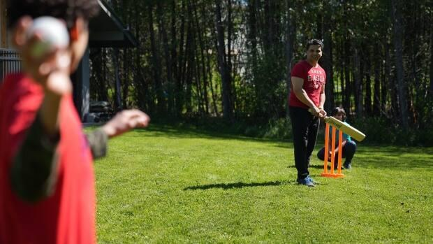 Akber Hussain and his children play cricket in their west Ottawa backyard on May 24, 2021. With the sport growing in popularity across Ontario, Hussain is calling for more cricket grounds to be built in the nation's capital. (Felix Desroches/CBC - image credit)