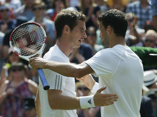Grigor Dimitrov of Bulgaria, right, shakes hands with defending champion Andy Murray of Britain after defeating him in their men's singles quarterfinal match at the All England Lawn Tennis Championships in Wimbledon, London, Wednesday July 2, 2014. (AP Photo/Pavel Golovkin)