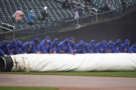 New York Mets employees roll a tarp over the field during a delay in the first inning of a baseball game against the Miami Marlins at Citi Field, Sunday, April 11, 2021, in New York. The game was delayed at the top of the first inning due to rain. (AP Photo/Seth Wenig)