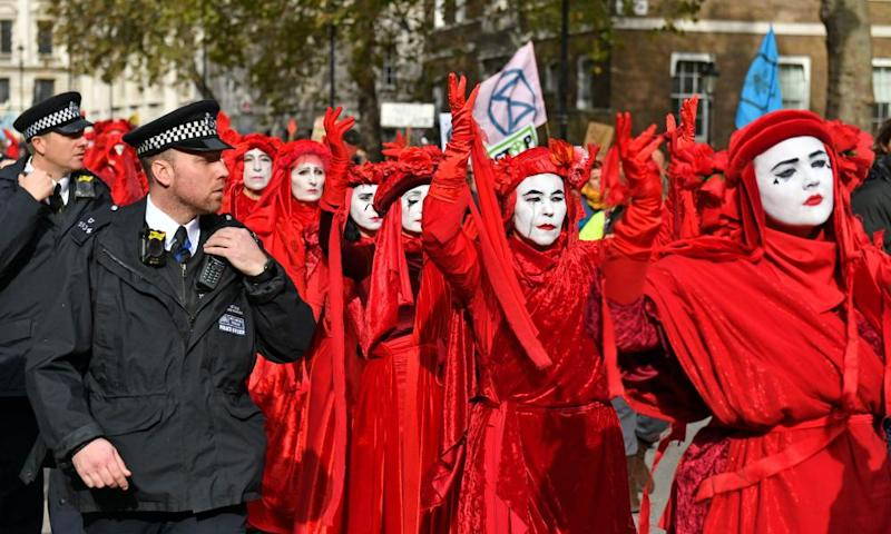 Police escort XR protesters on Whitehall in London.