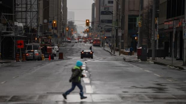 A child scampers across Albert Street in downtown Ottawa on Jan. 14, 2021, the first day under a stay-at-home order issued by the Ontario government to cut back spread of COVID-19. It has since been lifted. (Andrew Lee/CBC - image credit)