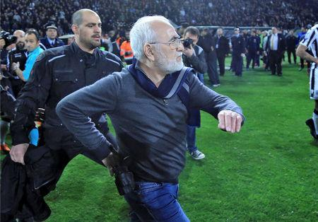 Russian-born Greek businessman and owner of PAOK Salonika, Ivan Savvides (C), pictured with what appears to be a gun in a holster, enters the pitch after the referee annulled a goal of PAOK during their soccer match against AEK Athens in Toumba Stadium in Thessaloniki, Greece, March 11, 2018. Intimenews via REUTERS