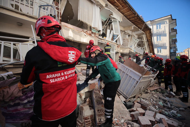 Rescuers searching for people buried under the rubble of a collapsed building, after an earthquake struck Elazig, eastern Turkey, Saturday, Jan. 25, 2020. Emergency workers and security forces distributed tents, beds and blankets as overnight temperatures dropped below freezing in the affected areas. Mosques, schools, sports halls and student dormitories were opened for hundreds who left their homes after the quake. (IHH/ Humanitarian Relief Foundation via AP)