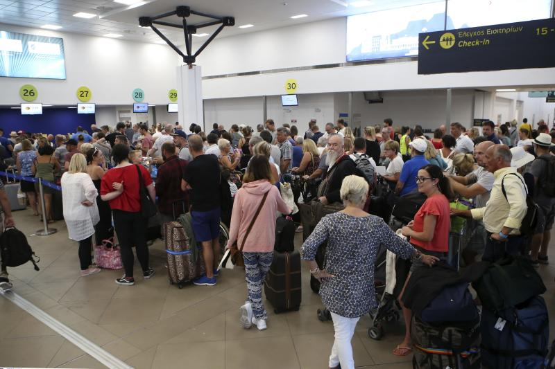 British tourists wait in a queue at the Ioannis Kapodistrias Airport in Corfu island, northwestern Greece, Monday, Sept. 23, 2019. Hundreds of thousands of travelers were stranded across the world Monday after British tour company Thomas Cook collapsed, immediately halting almost all its flights and hotel services and laying off all its employees. (Stamatis Katopodis/InTime News via AP)