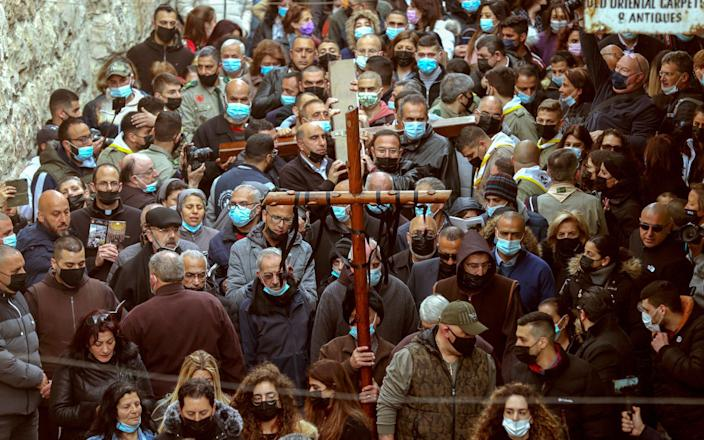 Christian worshipers carry a wooden cross along Via Dolorosa in the Old City of Jerusalem during the Good Friday procession-EMMANUEL DUNAND / AFP