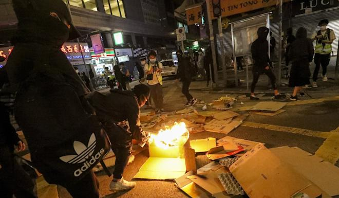 Demonstrators set cardboard alight in Yuen Long during a protest marking eight months since a group of men armed with poles indiscriminately beat anti-government protesters and bystanders at the local MTR station. Photo: Dickson Lee