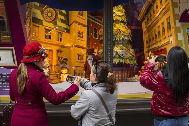 Pedestrians stop to look at holiday window displays at Macy's flagship store in New York