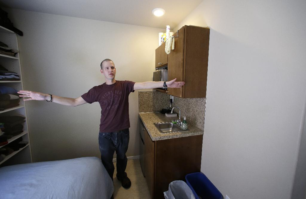 In this photo taken Wednesday, April 24, 2013, Kris King spreads his arms as he shows off his tiny apartment in Seattle. Even King was initially shocked by the size of the apartment he rented near downtown, roughly the size of large parking spot. Cities such as San Francisco, New York and Boston have been encouraging tiny apartments to cater to young workers, retirees others who prefer city dwelling, singles or students. San Francisco last fall approved construction of apartments as small as 220 square feet, while Boston has approved 300 new units as small as 375 sq. feet. But in Seattle, where city codes have allowed for even smaller micro-apartments and dozens have been built in the last five years, the trend is facing a backlash from some neighbors who are pushing for a building moratorium or for them to be more adequately regulated. (AP Photo/Elaine Thompson)