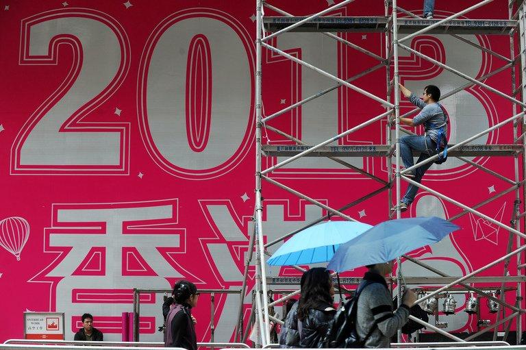 A worker prepares a promotional 2013 banner outside a shopping mall in Hong Kong on December 29, 2012