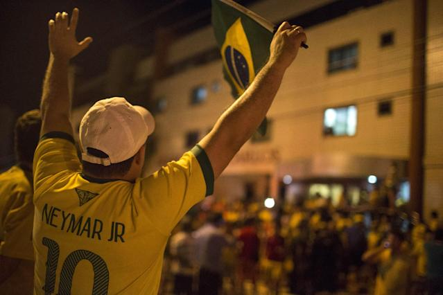 A Brazil soccer fan wearing a Neymar jersey waves a Brazilian flag outside Sao Carlos Hospital where Brazil's soccer player Neymar was taken after being injured during the World Cup quarterfinal soccer match against Colombia in Fortaleza, Brazil, Friday, July 4, 2014. Brazil's team doctor says Neymar will miss the rest of the World Cup after breaking a vertebrae during the team's quarterfinal win over Colombia. (AP Photo/Renata Brito)