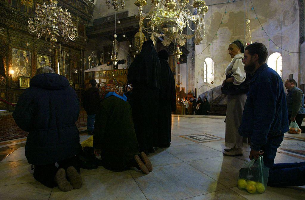 BETHLEHEM: Orthodox Christians kneel in prayer in the Church of the Nativity. File photo: 2003