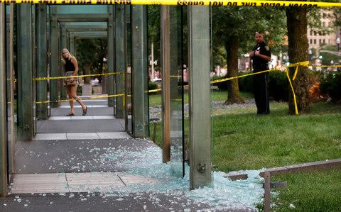A passerby, left, and a law enforcement official, right, stand near broken glass at the New England Holocaust Memorial on Monday, Aug. 14, 2017, in Boston - Credit: AP