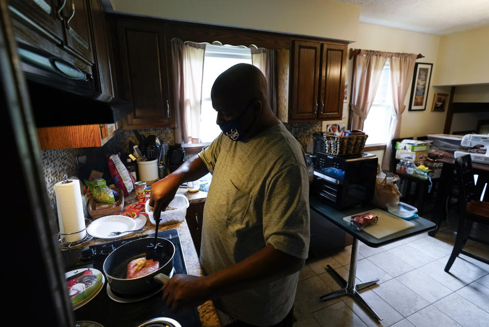 Larry Brown cooks dinner at his parents house, Thursday, Aug. 27, 2020, in Indianapolis. Brown's has his kids chop ingredients so he can make favorite meals, meatloaf or baked mac and cheese. He's not yet comfortable gripping a knife, or even holding a pen like he used to. (AP Photo/Darron Cummings)
