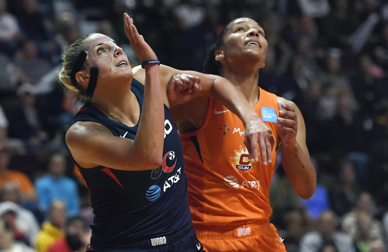 Washington Mystics' Elena Delle Donne, left, and Connecticut Sun's Jasmine Thomas fight for position under the basket during the first half in Game 4 of basketball's WNBA Finals, Tuesday, Oct. 8, 2019, in Uncasville, Conn. (AP Photo/Jessica Hill)