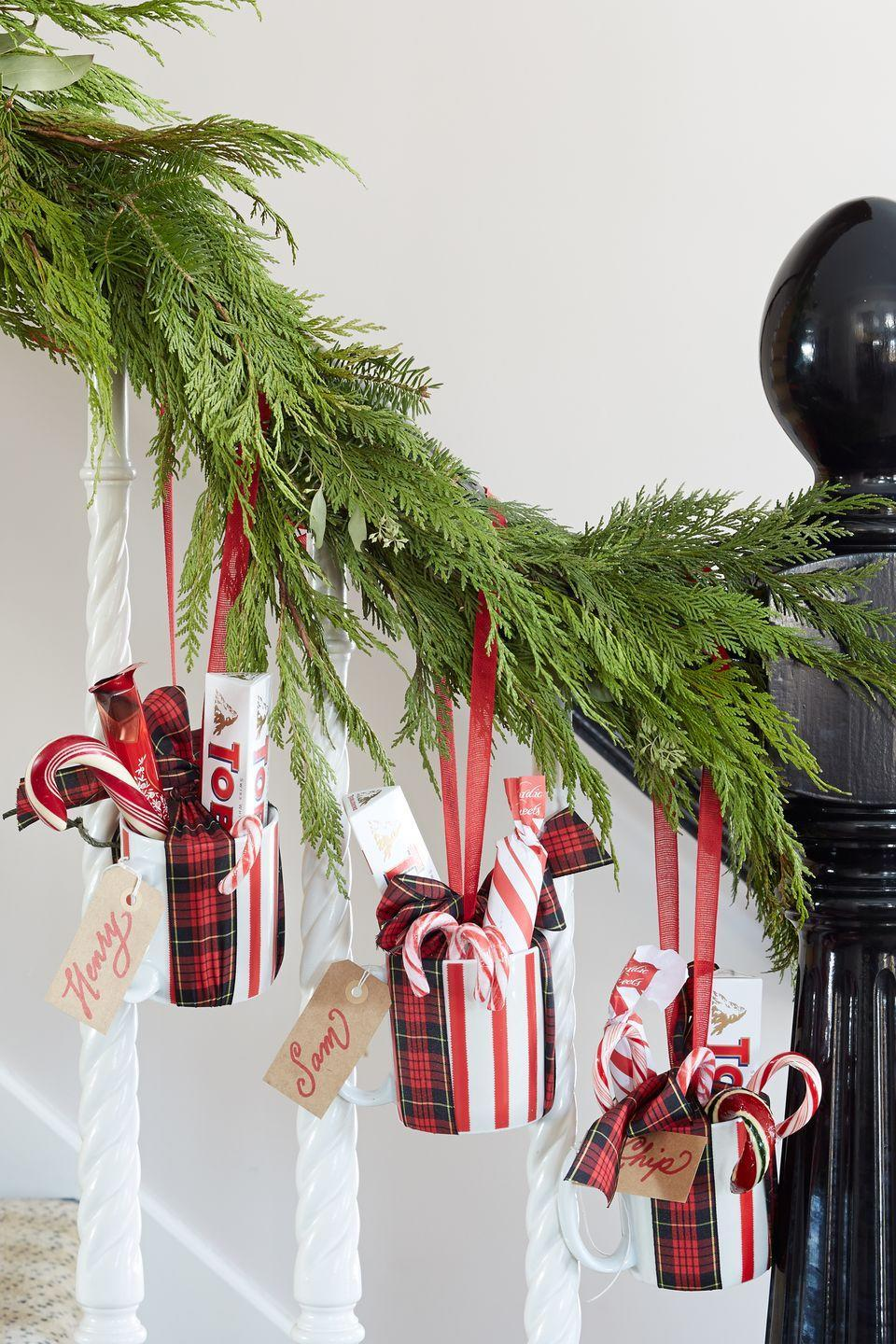 """<p>Sweeten a garland with welcome gifts. Offer treats to overnight guests as they head up to their temporary digs by hanging coffee mugs filled with candy and hot cocoa mix on the banister garland.</p><p><a class=""""link rapid-noclick-resp"""" href=""""https://www.amazon.com/s/ref=nb_sb_noss_2?url=search-alias%3Daps&field-keywords=plaid+coffee+mug&rh=i%3Aaps%2Ck%3Aplaid+coffee+mug&tag=syn-yahoo-20&ascsubtag=%5Bartid%7C10050.g.1247%5Bsrc%7Cyahoo-us"""" rel=""""nofollow noopener"""" target=""""_blank"""" data-ylk=""""slk:SHOP COFFEE MUGS"""">SHOP COFFEE MUGS</a></p>"""