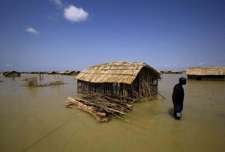 A South Sudanese refugee tries to repair his hut in flooded waters from the White Nile at a refugee camp which was inundated after heavy rain near in al-Qanaa, on September 14, 2021 (AFP/ASHRAF SHAZLY)