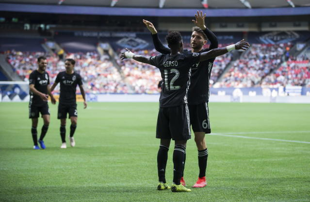 Sporting Kansas City's Ilie Sanchez (6) and Gerso Fernandes (12) celebrate after the Vancouver Whitecaps scored an own goal during the first half of an MLS soccer match Saturday, July 13, 2019, in Vancouver, British Columbia. (Darryl Dyck/The Canadian Press via AP)