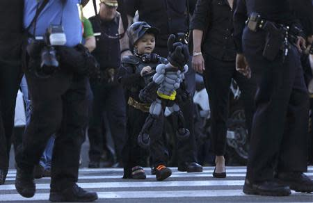 """Five-year-old leukemia survivor Miles Scott, dressed as """"Batkid"""" looks at a Batman balloon after a ceremony arranged by the Make- A - Wish Foundation in San Francisco, California November 15, 2013. REUTERS/Stephen Lam"""