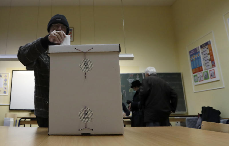 A voter casts his ballot at a polling station in Zagreb, Croatia, Sunday, Jan. 5, 2020. Voters in Croatia on Sunday cast ballots to choose a new president in a fiercely contested runoff race, with a liberal opposition candidate posing a challenge to the conservative incumbent as the country presides the European Union during a crucial period. (AP Photo/Darko Vojinovic)