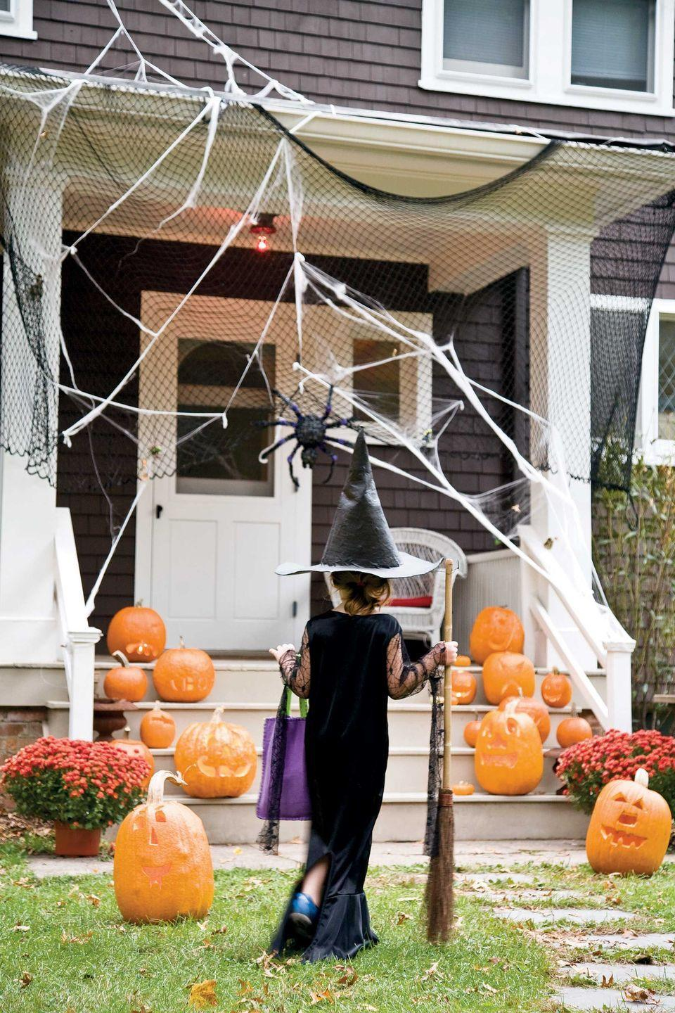 <p>Two rows of jovial jack-o-lanterns guide cautious guests toward the door. Soccer goal netting is draped halfway over the roof, offering a clever method to attach webs and giving one spider a fun way to greet newcomers.</p>