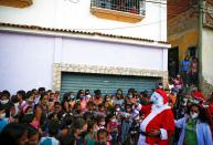 Man dressed up as Santa Claus greets residents in a low-income neighbourhood in Guarenas