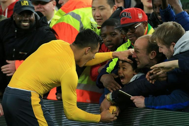 Arsenal's striker Alexis Sanchez gives his match shirt to a young fan following a win over Middlesbrough on April 17, 2017