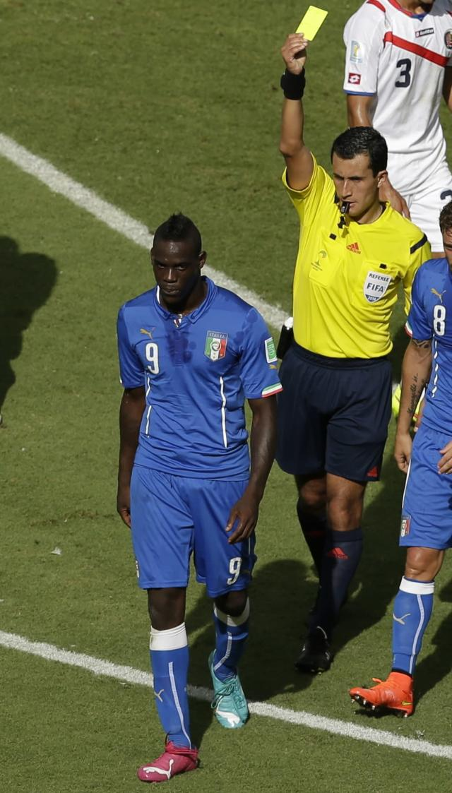 Italy's Mario Balotelli, left, is booked by referee Enrique Osses from Chile during the group D World Cup soccer match between Italy and Costa Rica at the Arena Pernambuco in Recife, Brazil, Friday, June 20, 2014. (AP Photo/Hassan Ammar)