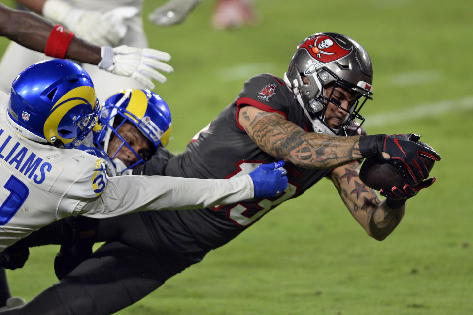 Tampa Bay Buccaneers wide receiver Mike Evans (13) slips a tackle by Los Angeles Rams defensive back Darious Williams (31) to score during the first half of an NFL football game Monday, Nov. 23, 2020, in Tampa, Fla. (AP Photo/Jason Behnken)