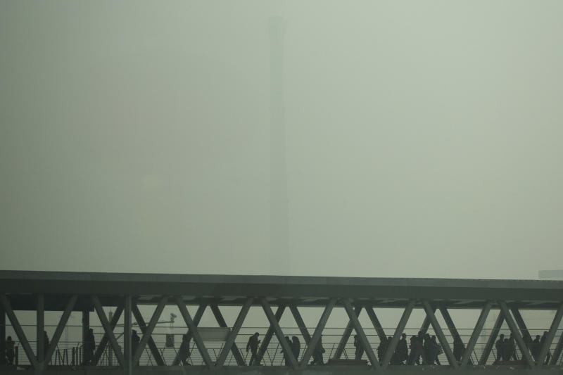 A chimney of a heating plant is obscured by heavy haze as commuters walk through a bridge linking a subway station and a bus station on a severely polluted day in Beijing Tuesday, Feb. 25, 2014. Beijing remained cloaked in hazardous white pollution hiding much of its skyline Tuesday. (AP Photo/Alexander F. Yuan)