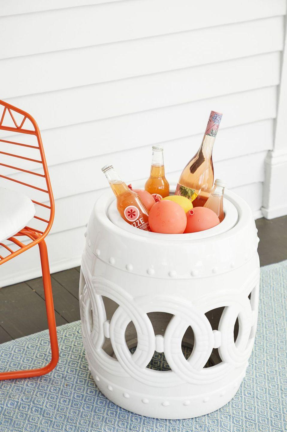 <p>Take a garden stool — bird baths work too! — and fill it with frozen water balloons for a party-ready cooler. They'll melt slower than traditional ice cubes, so guests won't have to dunk their hands in water to refuel. </p>
