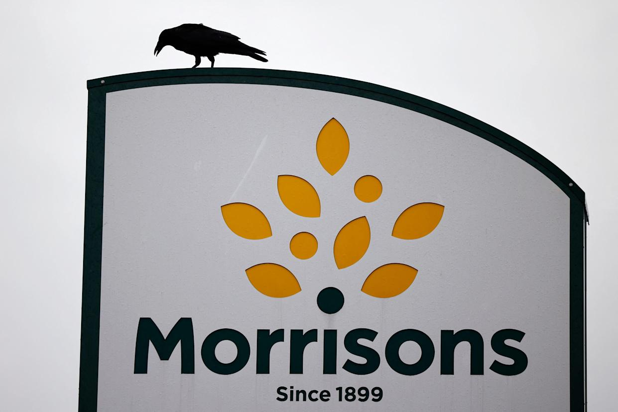 A bird is perched on a Morrisons sign outside its supermarket in Stratford, east London on June 21, 2021. - Shares in British supermarket chain Morrisons surged today after it rejected a £5.5-billion ($7.6-billion, 6.4-billion-euro) takeover approach as too low. (Photo by Tolga Akmen / AFP) (Photo by TOLGA AKMEN/AFP via Getty Images)