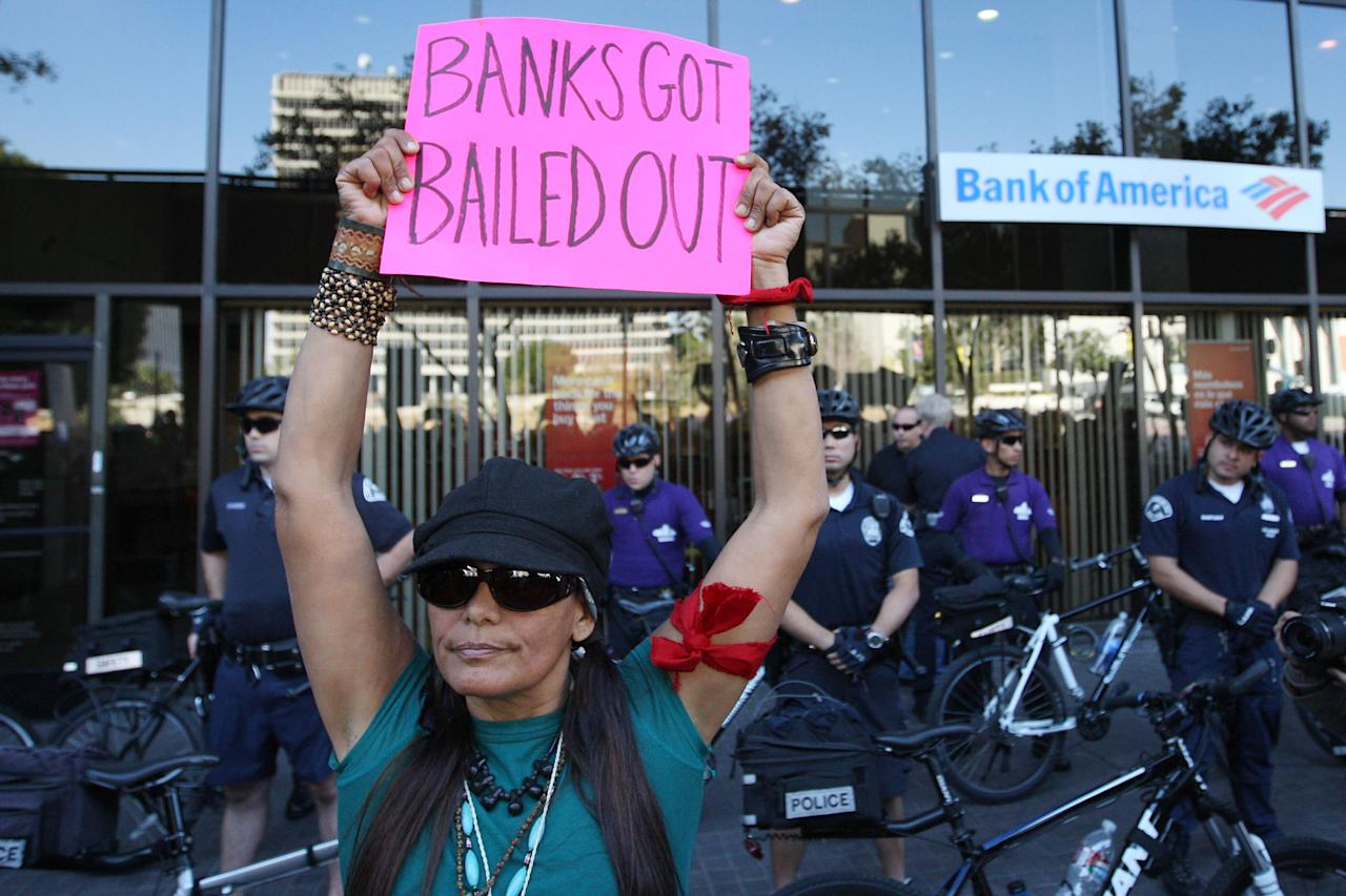 LOS ANGELES, CA - NOVEMBER 5:  Police officers stand guard as Occupy LA protesters stop to demonstrate at a Bank of America during the Move Your Money March on what is being called Bank Transfer Day on November 5, 2011 in Los Angeles, California. Occupy movement members are calling for people to move their money from banks to credit unions today in support of the 99% movement.   (Photo by David McNew/Getty Images)