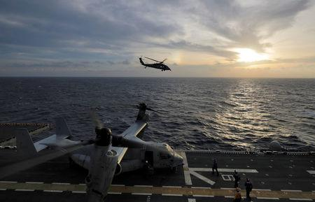 A Navy MH-60S Seahawk helicopter heads out at sunrise on a search and rescue mission from the USS Kearsarge as MV-22 Ospreys prepare on the flight deck as operations to assist hurricane-ravaged St. Croix and Puerto Rico begin, in the Caribbean Sea,  September 21, 2017.  REUTERS/Jonathan Drake