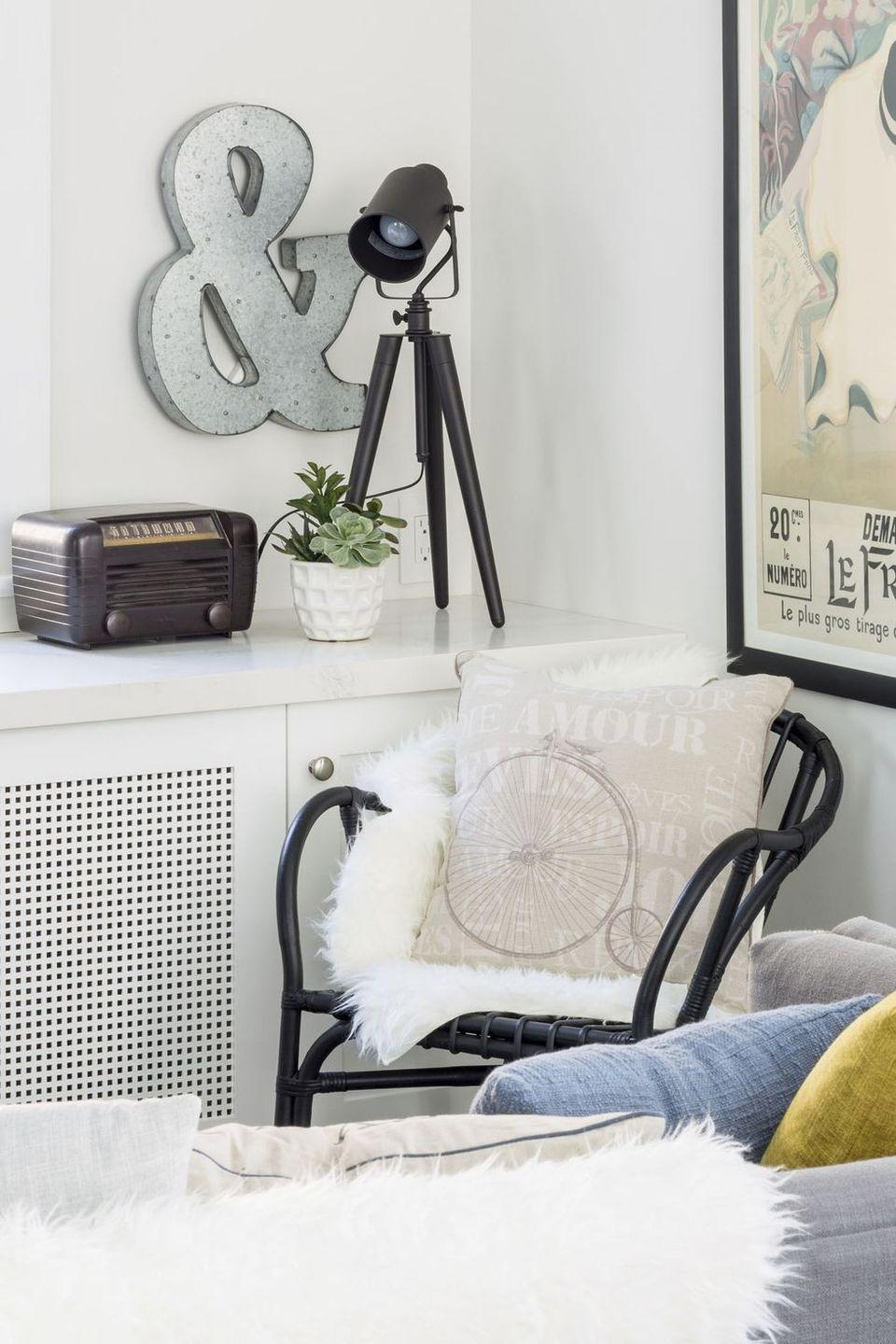 <p>This reading nook benefits from tripod-style lighting and seating dressed in a cozy white rug. </p>