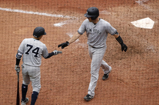 New York Yankees' Austin Romine, right, celebrates with Ronald Torreyes (74) after hitting a solo home run during the ninth inning of a baseball game against the Kansas City Royals, Sunday, May 20, 2018, in Kansas City, Mo. (AP Photo/Charlie Riedel)