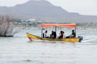 People ride a boat during an excursion at a dam in Sayyan near Sanaa