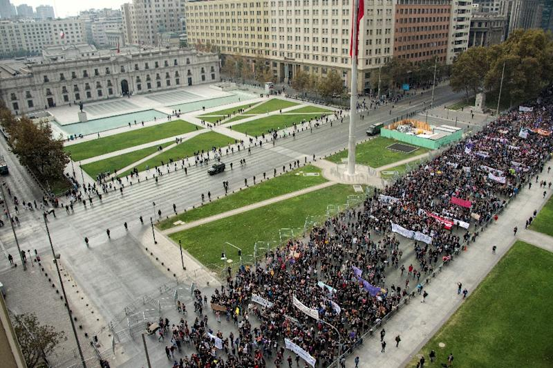 Women students pass in front of La Moneda presidential palace to protest sexist education and the slow pace of Chilean educational reform