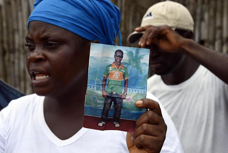 Liberian mother Mary holds a picture of her son Emaya, 20, who is suffering from Ebola and being treated at Island Hospital in Monrovia on September 26, 2014 (AFP Photo/Pascal Guyot)
