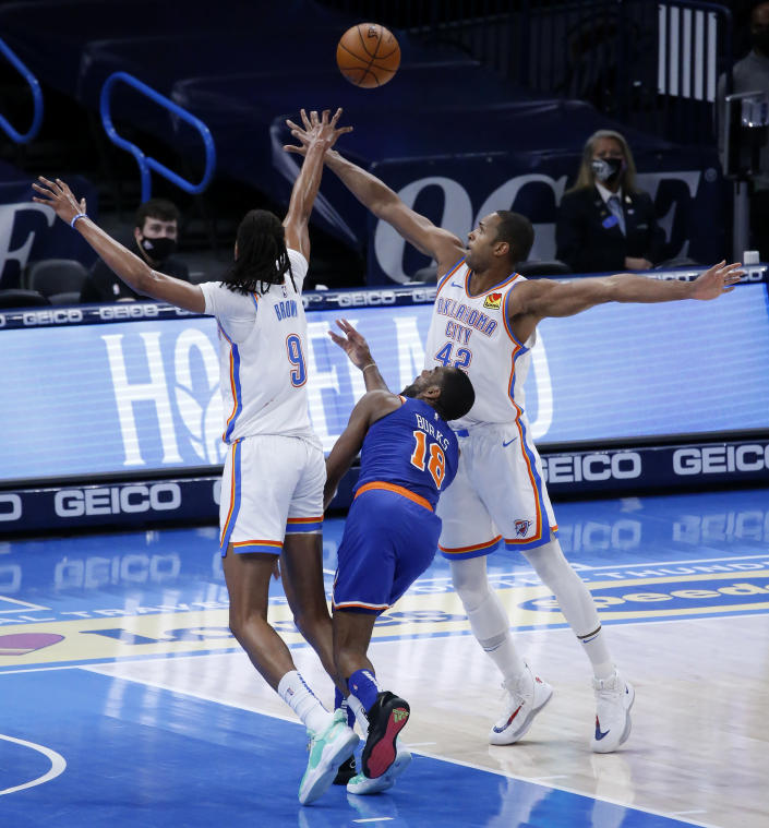 New York Knicks guard Alec Burks (18) goes against Oklahoma City Thunder center Moses Brown (9) and center Al Horford (42) during the first half of an NBA basketball game, Saturday, March 13, 2021, in Oklahoma City. (AP Photo/Garett Fisbeck)