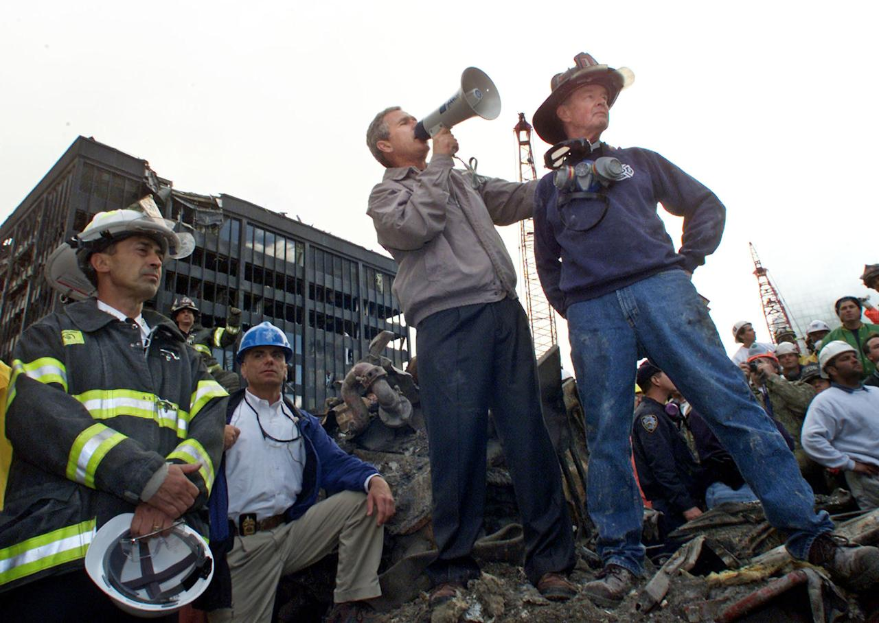 Bush is shown with retired firefighter Bob Beckwith (R) at the scene of the World Trade Center disaster on September 14, 2001. (REUTERS/Win McNamee-Files RC/HB)
