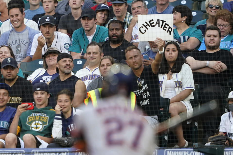 """A fan holds up a sign that reads """"cheater"""" as Houston Astros' Jose Altuve bats during the second inning of the team's baseball game against the Seattle Mariners, Tuesday, July 27, 2021, in Seattle. (AP Photo/Ted S. Warren)"""